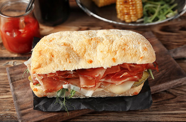 Tasty sandwich with prosciutto on wooden board