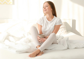 Beautiful young smiling woman with coffee on bed at home