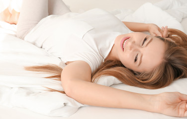Beautiful young smiling woman on bed at home