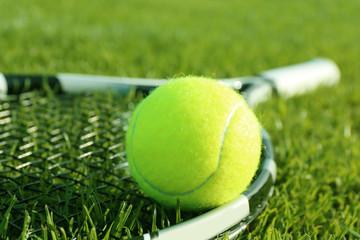 Tennis racket and ball on green grass