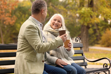 Happy mature couple resting on bench in park
