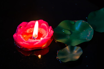 Floating red candle in a pond