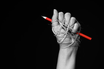 Hand with red pencil tied with rope, depicting the idea of freedom of the press or freedom of expression on dark background in low key. international human rights day concept. Wall mural