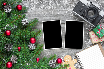 retro camera and christmas blank photo frames with fir tree branches, decorations, gift boxes and lined notebook