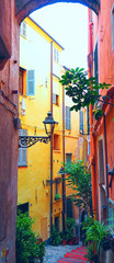 Narrow medieval, old street with flowers in San Remo, Liguria, Italy