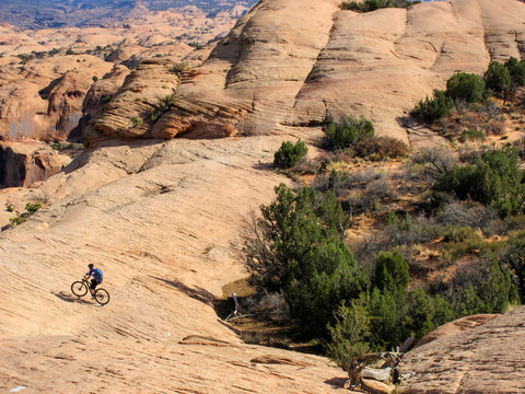 Mountain biker in a valley at Slickrock mountain biking trail in Moab, Utah