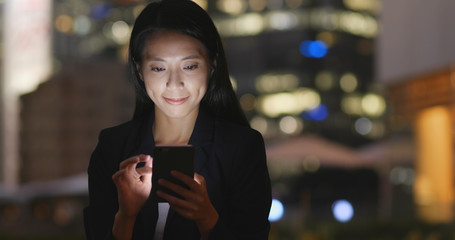 Businesswoman use of smart phone at night