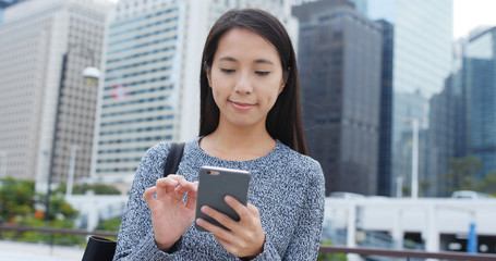 Woman looking at cellphone in city