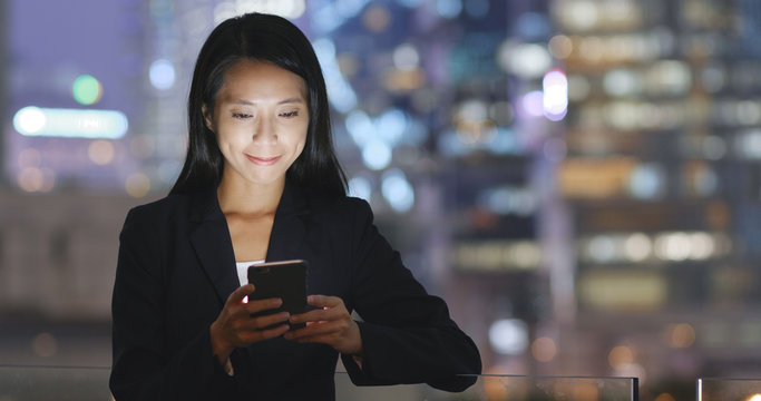 Business woman looking at cellphone in city