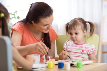 woman teaches kids painting at kindergarten or playschool