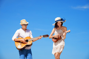 couple lovers in romantice honeymoon playing guitar together on the sea beach in daylight and blue cleared sky in background