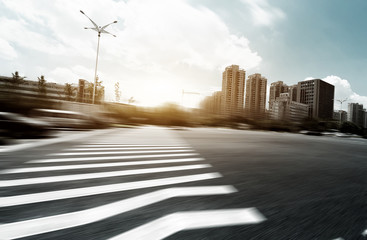 empty asphalt road in modern city with sunbeam