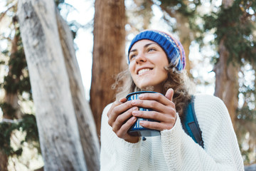 Traveling beautiful woman with knitted hat drinking hot coffee from a mug and smiling in wild forest at sunny day. Portrait. Laughing