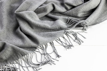 Background texture of the crumpled gray winter fashionable female scarf. On a white wooden table