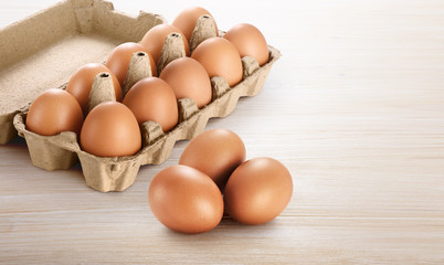 Carton egg box with eggs on a wooden background.