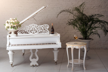 Grand piano in a luxury white classic interior with wine, palms and flowers.