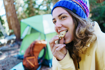 Pretty woman tourist eating snack and camping in the wild