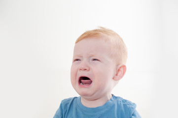 Redhead boy crying against white background