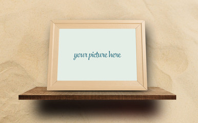Empty wooden photo frame on sandy background for mock up