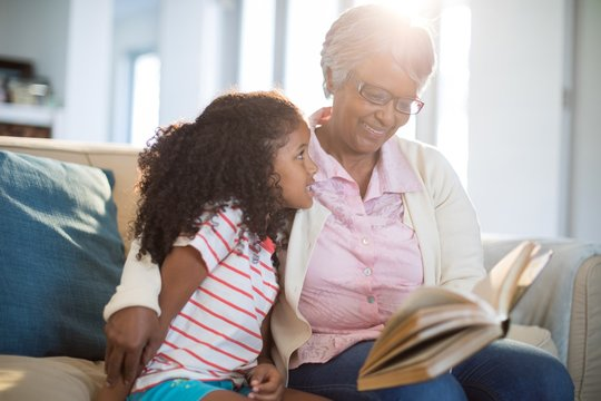 Grandmother and daughter reading book in living room