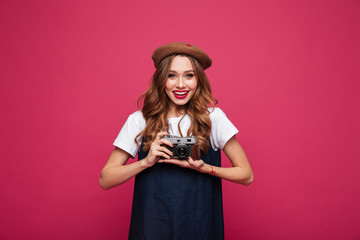 Smiling positive lady holding retro camera in hands and looking camera