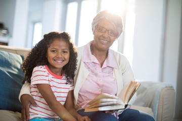Smiling grandmother and daughter reading book in living room