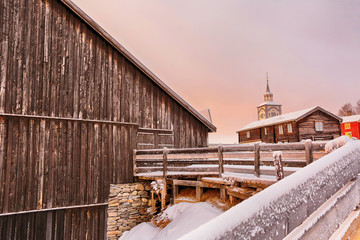Winter in Roeros, the view of the old wooden church and Roeros Museum building during colorful winter sunrise