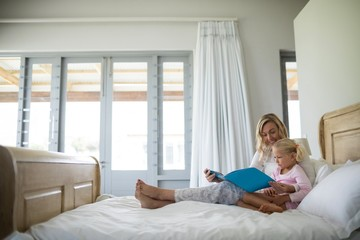 Mother and daughter reading story book in the bedroom