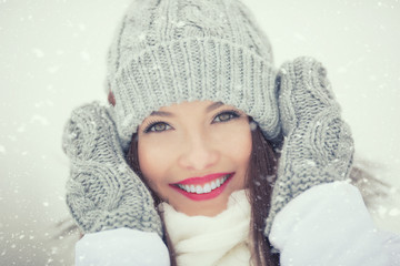 Beautiful smiling young woman in warm clothing. The concept of portrait in winter snowy weather