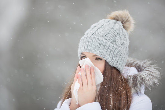 Girl with allergy symptom blowing nose. Teen girl using a tissue in a winter park