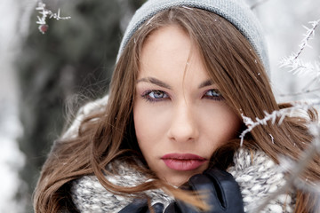 Winter portrait of beautiful young woman in park looking at camera.