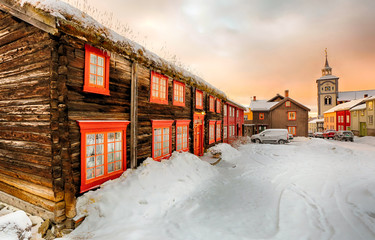 Winter in Roeros, the street with old timber houses and wooden church during colorful winter sunrise