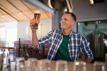 Smiling man having glass of beer at counter