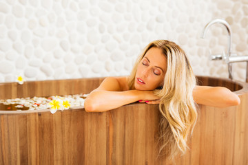 Young woman relaxing in wooden bath