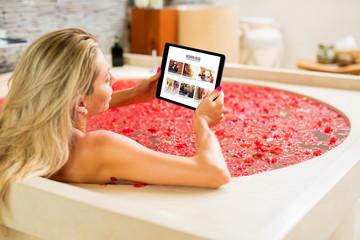 Woman reading on tablet while taking bath