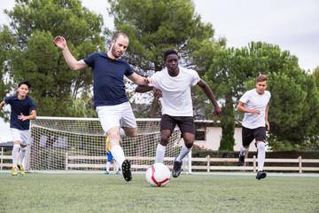 Sportive multiracial group of football players kicking ball round green stadium.