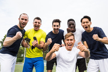 Group of diverse young sportsmen screaming with determination while posing cheerfully at camera.