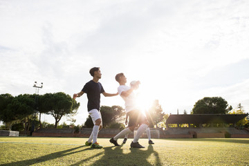 View of sportive men running on green grass catching and kicking football in bright sunlight.
