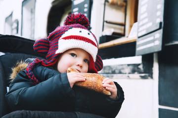 Child eating Trdlo or Trdelnik - Traditional National Czech Sweet Pastry Dough.