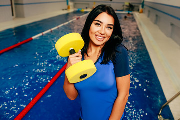 Sporty woman holding Aqua aerobics stuff on the background swimming pool. Aqua fitness instructor