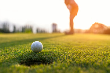 Golfer asian woman putting golf ball on the green golf on sun set evening time, select focus. Healthy and Lifestyle Concept.