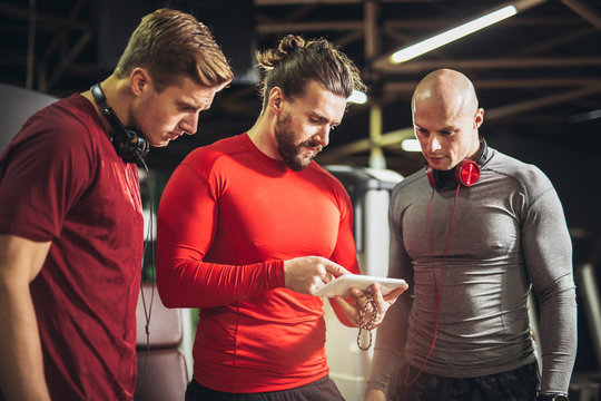 Young men and their personal fitness trainer in the gym, shows them a training plan on the phone
