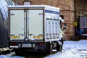 Old broken cargo car truck near industrial buildings