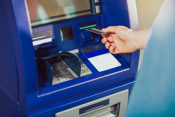 Man uses an ATM card inserted into the ATM machine for cash.