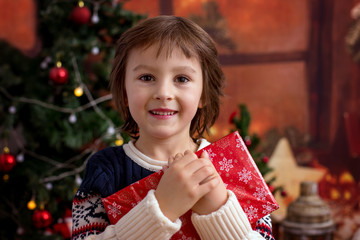 Cute preschool boy, holding christmas present, joy and happiness