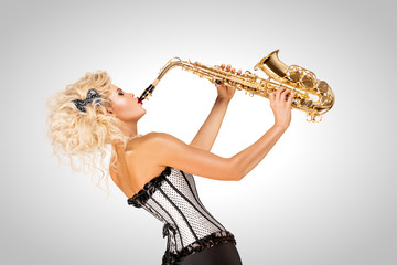 Playing jazz / Beautiful pinup model playing saxophone on grey background.
