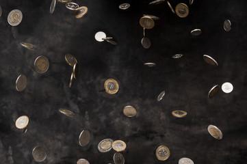 Rain of polish coins on dark background