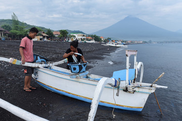 A woman collects fish from a fishing boat after it arrived on shore as Mount Agung is seen in the background from Amed, Karangasem