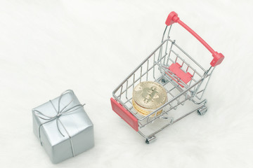 Bitcoin coins in shopping cart and gifts. White background