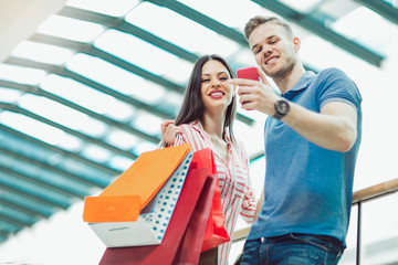Happy young couple with shopping bags and smartphone talking in mall